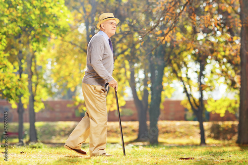 Smiling senior gentleman walking with a cane in a park Fototapet