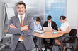 Businessman With Arm Crossed Standing In Front Of His Colleagues