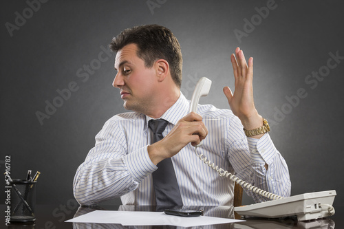Valokuva  Businessman having a talk to the hand gesture during phone call