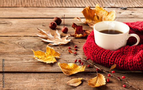 Tuinposter Herfst Hot coffee and autumn leaves on vintage wood background