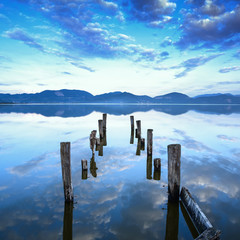 Fototapeta Molo Wooden pier or jetty remains on a lake sunset. Tuscany, Italy