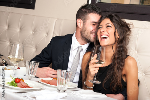Attractive elegant young couple drinking a cocktail at the resta