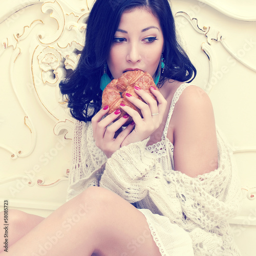 Fotografie, Obraz  Young beautiful woman eating her french croissant