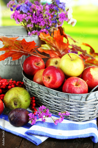 Fruits Juicy apples in basket on table on natural background