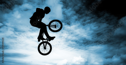 Man doing an jump with a bmx bike over blue sky background. Wallpaper Mural