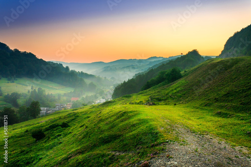 Poster de jardin Colline hillside near the village in morning mist