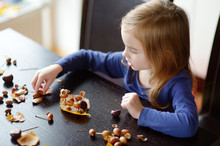 Little Girl Making Chestnuts Creatures