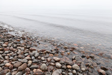 Stones On Saimaa Lake Coast In Foggy Morning