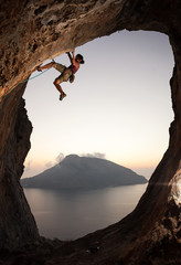 Female rock climber at sunset, Kalymnos Island, Greece