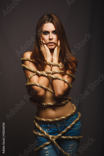 Photo brunette woman bound with rope prisoner in jeans on a gray backg