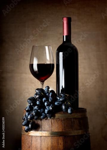 czerwone-wino-z-beczki-i-granatowe-winogrona-na-brazowym-tle