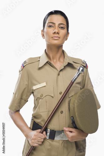Fototapeta Portrait of a female police officer holding a stick