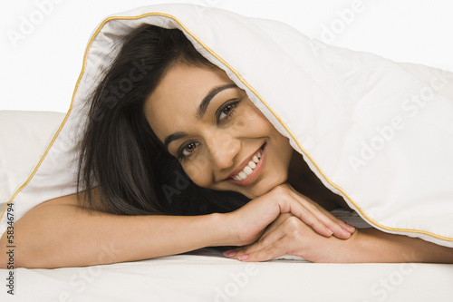 Photo  Portrait of a woman looking through a quilt