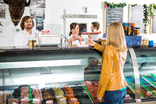 Fényképezés Saleswoman Giving Meat To Female Customer