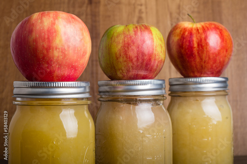 Photo Jars of homemade applesauce with apples