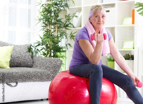 Foto  Glückliche ältere Frau, die auf Gymnastikball und Übung sitzt