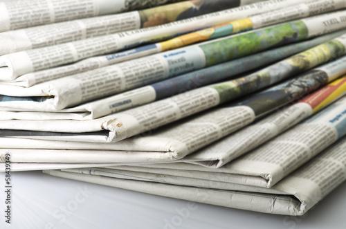 Fotografía Pila de Varios periódicos sobre fondo blanco.