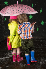 Little Girl And Boy Hiding Under Umbrella, View From Back