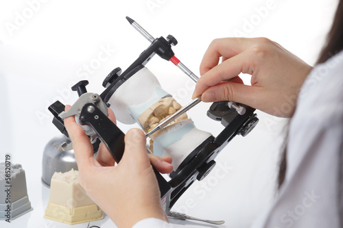 Valokuvatapetti Dental technician working with articulator in dental laboratory