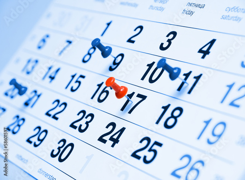 Fotografía  Portarretrato de una página de calendario azul tonificado con chinchetas