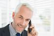 Close-up of smiling mature businessman using cellphone