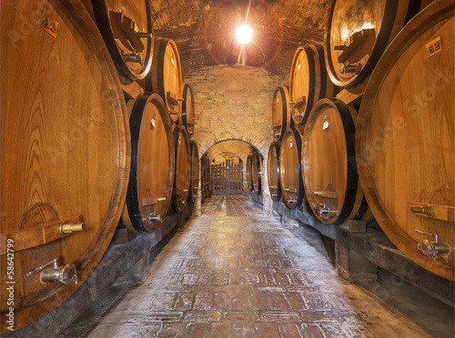 Wine barrels stacked in the old cellar of an Italian winery. Canvas Print