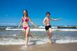 Teenage girl and boy running, jumping on beach