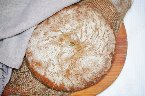 Fotografie, Obraz  Rustic cornmeal and rye bread loaf, whole dusted with flour