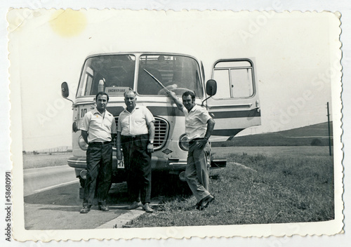 Tela CIRCA 1960: Men standing in front of the bus, on the road