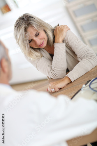 Patient seing doctor for shoulder articulation pain Canvas Print