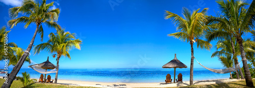 Poster Strand Tropical beach panorama with chairs and umbrellas