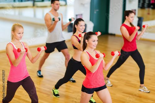 group of smiling people working out with dumbbells