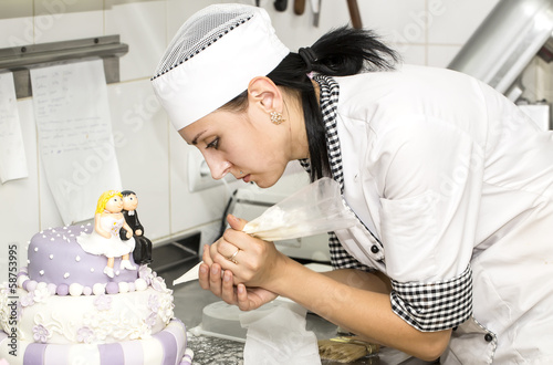 pastry chef decorates a cake in a candy store Canvas-taulu