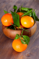 Tangerines in a bowl on wooden background