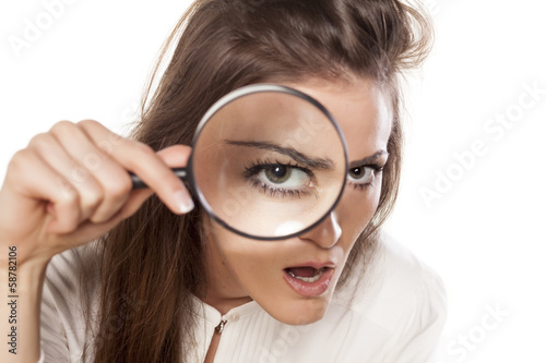 Fotografía  shocked young woman looking through a magnifying glass