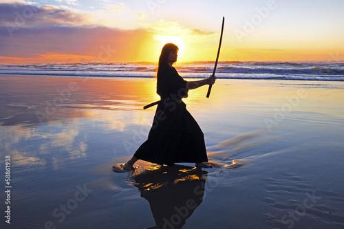 Foto  Young samurai women with Japanese sword(Katana) at sunset on the