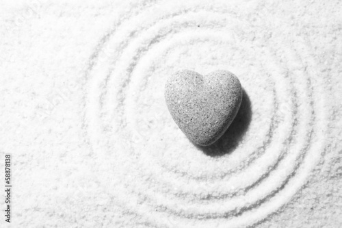 Fotobehang Stenen in het Zand Grey zen stone in shape of heart, on sand background