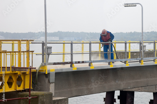 Fényképezés Worker sandblasting barrier on the waterfront.