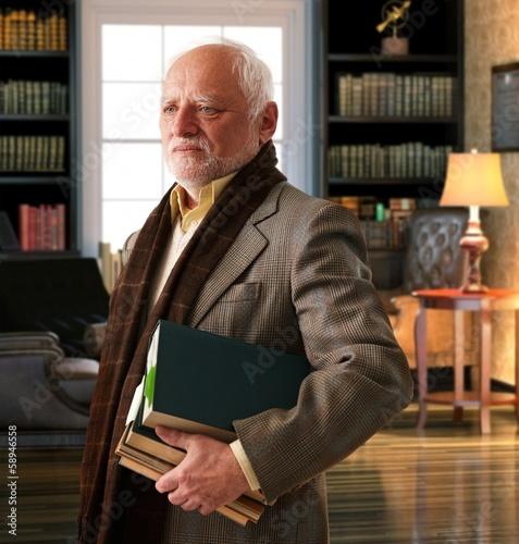Elderly professor with books at library room Fototapeta
