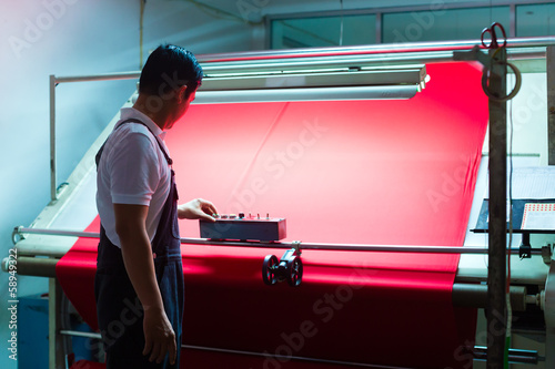 Obraz Asian worker controls fabrics in textile plant - fototapety do salonu