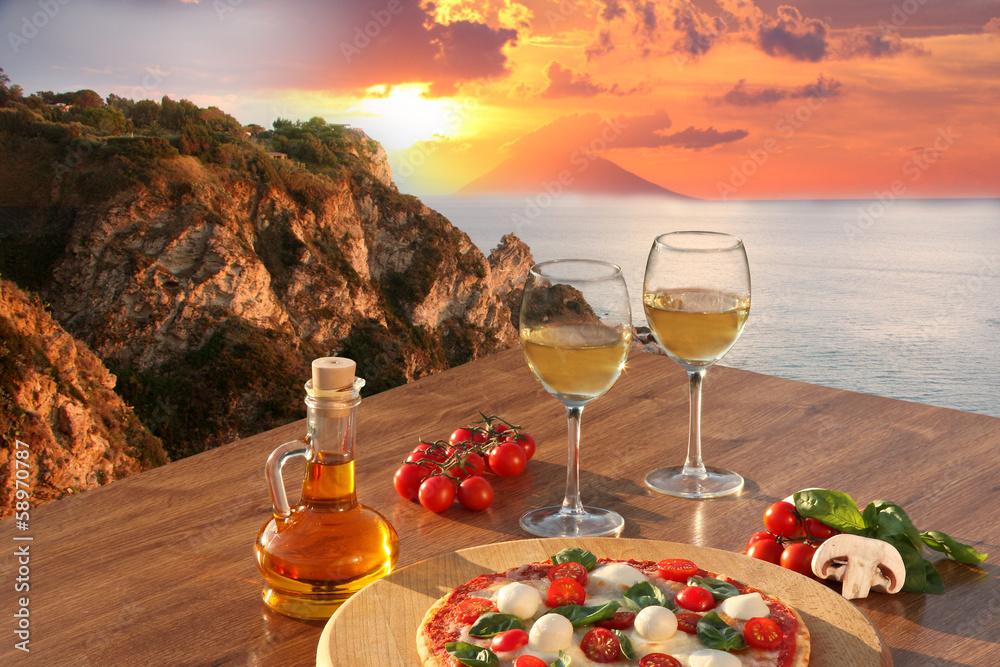 Fototapeta Italian pizza and glasses of wine against Calabria coast, Italy