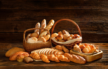 Fototapeta Do piekarni Variety of bread in wicker basket on old wooden background.