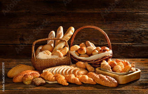 Variety of bread in wicker basket on old wooden background. - 58970791