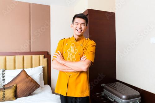 Fotografie, Obraz  Asian Chinese porter bringing suitcase to luxury hotel room