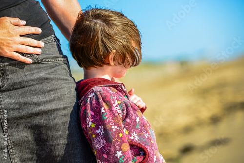 Fototapeta young child tight against her mother watching the sea beyond