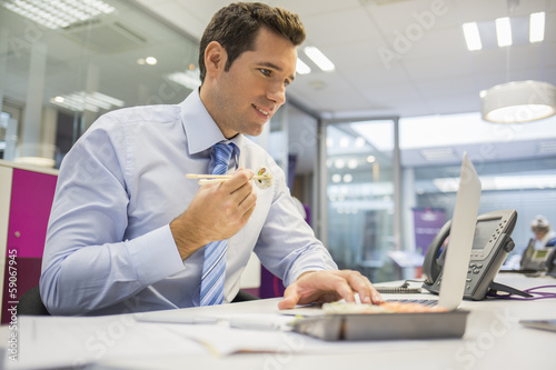 Businessman with laptop eating sushi on desk