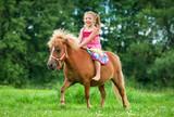 Little girl riding little pony