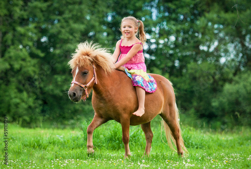 Photo Little girl riding little pony