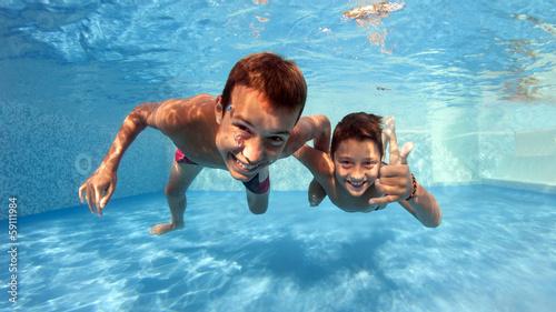 Valokuva  Underwater brothers portrait in swimming pool.