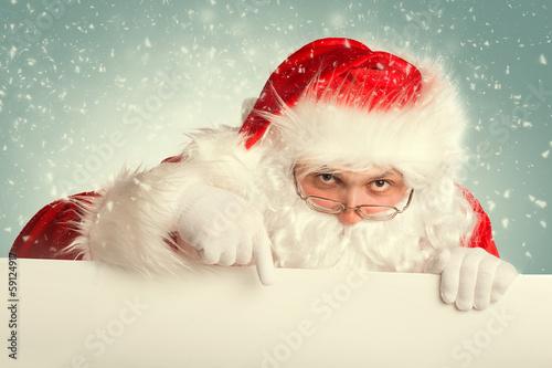 Foto-Doppelrollo - Santa Claus in a snow pointing to white blank banner (von tananddda)